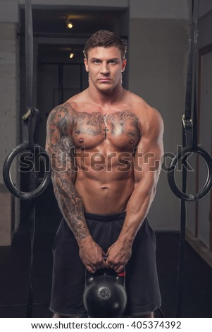 Muscular tattooed man holds lifting weight.