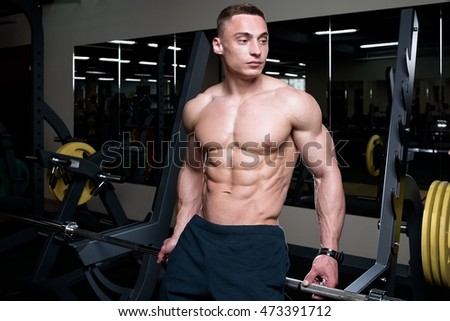 Muscular topless man sitting topless on the barbell in the gym