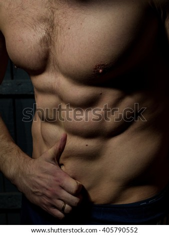 Muscular torso of young man with sexy body showing thumb up