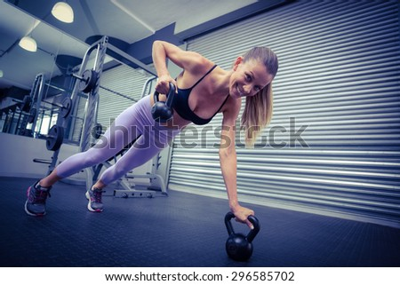 Muscular woman doing pushups while pulling kettlebells - stock photo
