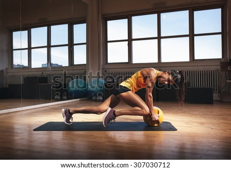 Muscular woman in gym working out on her core body. Strong woman exercising with kettlebell in sports club. - stock photo