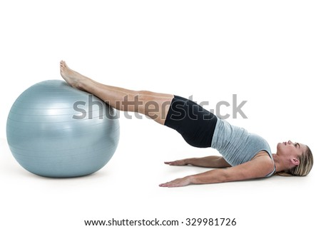 Muscular woman lying on floor with legs on exercise ball
