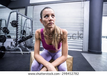 Muscular woman sitting on a wooden box with arms crossed