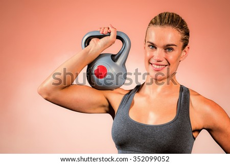 Muscular woman swinging heavy kettlebell against peach background