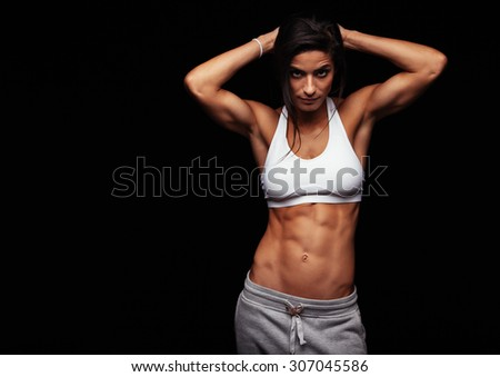 Muscular woman wearing fitness clothing posing against black background. Caucasian female model with perfect abs. - stock photo