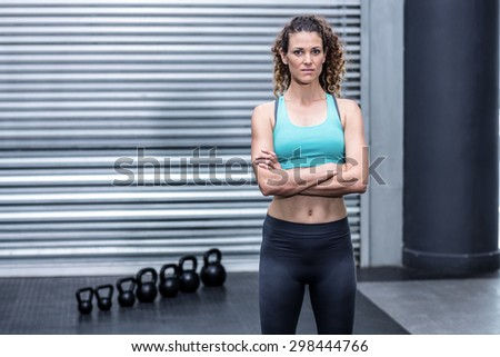 Muscular woman with hands on hips and kettlebells besides - stock photo