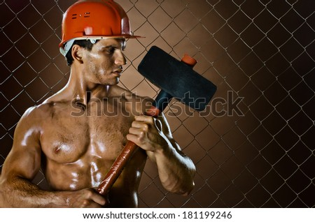 muscular worker , in  safety helmet  with big tup  in hands, on netting fence background - stock photo