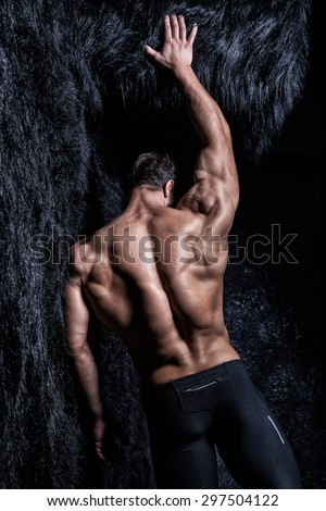 Muscular young athletic sexy man posing back - stock photo