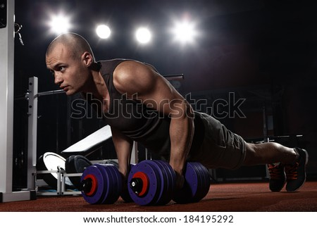 Muscular young bodybuilder pushing up on floor - stock photo