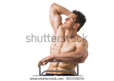 Muscular young bodybuilder sitting on chair, looking up. Isolated on white background - stock photo