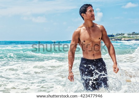 Muscular young Hawaiian man walking in the surf, making a splash