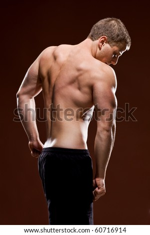Muscular young male showing his back muscles - stock photo