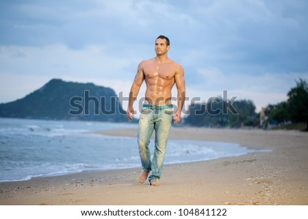 Muscular young male walking along a beach - stock photo