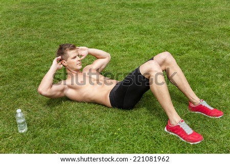 Muscular young man doing crunches outdoors - stock photo