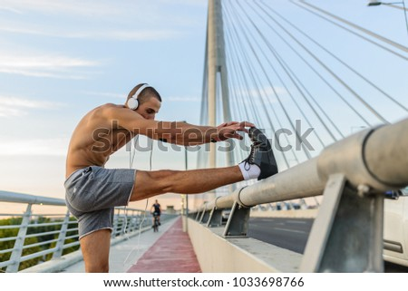 Muscular young man during his workout on the street. Fit, fitness, workout, exercise, dips and healthy lifestyle concept.