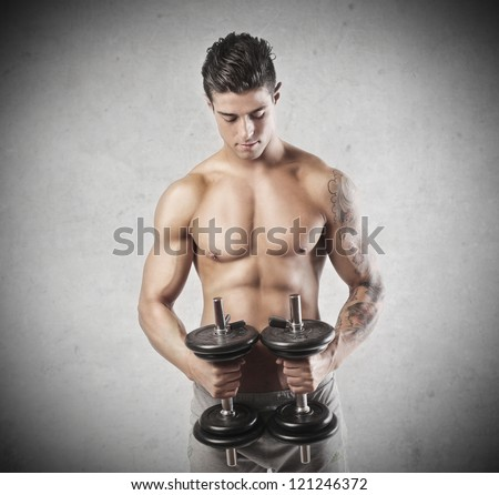 Muscular young man holding two dumbbells - stock photo