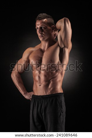 Muscular young man in studio on dark background shows the different movements and body parts