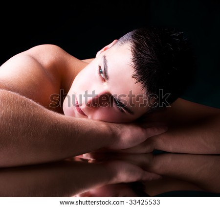 muscular young man lying on his hands, studio shot - stock photo