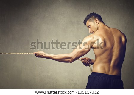 Muscular young man pulling a rope