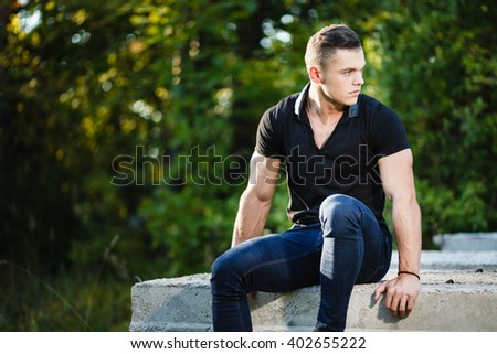 Muscular young man sitting on concrete slab - stock photo
