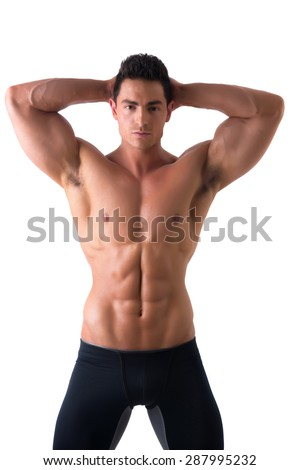 Muscular young man standing and looking at camera smiling, shirtless, wearing tight black shorts - stock photo