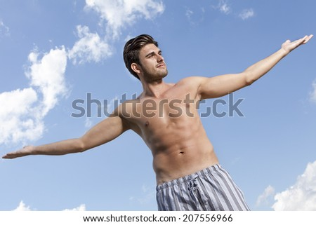 Muscular young man standing arms outstretched against cloudy sky - stock photo