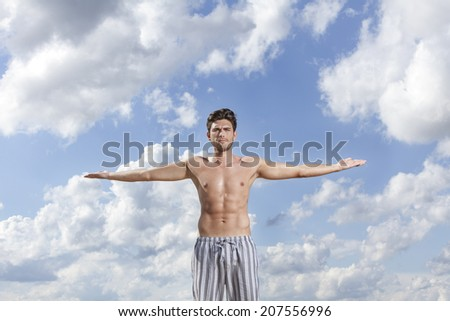 Muscular young man standing with arms wide open against cloudy sky - stock photo