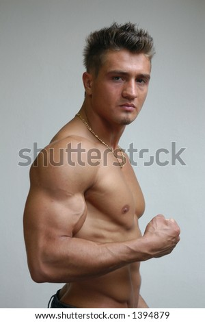 Muscular young model flexing biceps - stock photo