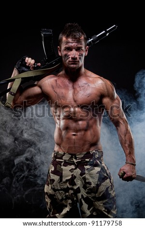 Muscular young sexy naked dirty soldiers with knife and weapons in army clothes and in camouflage paint - stock photo