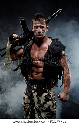Muscular young sexy naked soldiers with knives and weapons in army clothes and flak jacket in the smoke