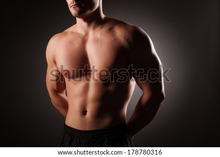 Muscular young sexy nude man on studio