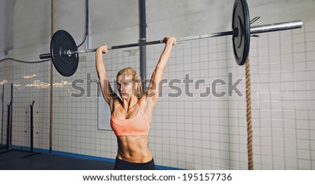 Muscular young woman doing weightlifting at crossfit gym. Fit female model lifting heavy weights at gym. - stock photo