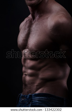 Musculed model isolated on dark background - stock photo