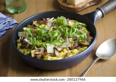 Mushroom and pancetta risotto topped with rocket and shaved Parmesan - stock photo