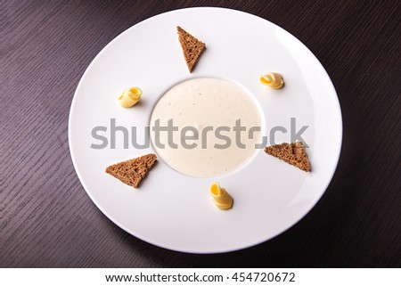mushroom cream soup in white plate on a wooden table. on the edges of the plates are toasted rye bread and butter. - stock photo