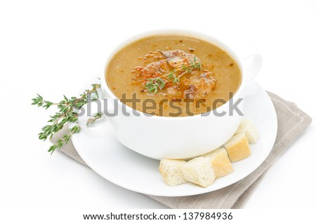 Mushroom soup in a bowl with croutons and thyme isolated on a white background