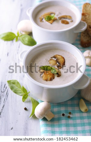 Mushroom soup in white pots, on napkin,  on wooden background - stock photo