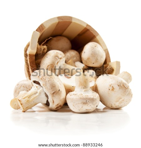 mushrooms champignon scattered from a wooden bucket  isolated on a white background - stock photo