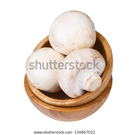 Mushrooms in a wooden bowl isolated on white background