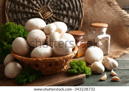 Mushrooms in basket on wooden surface - stock photo