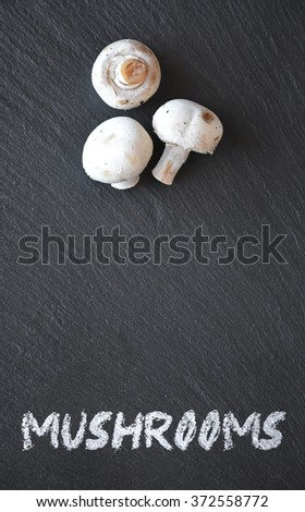Mushrooms on a black slate table ready to be used - stock photo