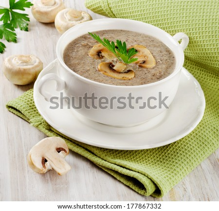 Mushrooms soup in a white bowl. Selective focus