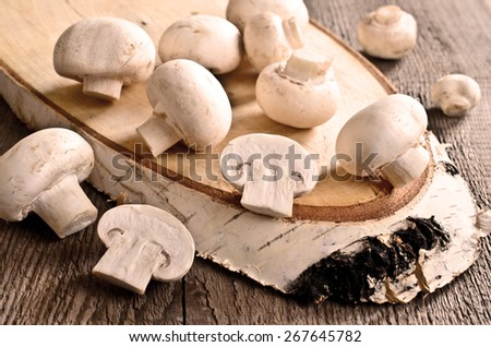 Mushrooms whole and sliced on a wooden surface - stock photo