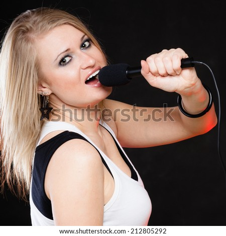 Music and entertainment concept - girl singer performer singing to microphone on black - stock photo
