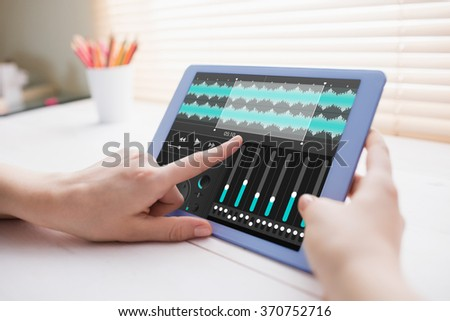 Music app against cropped image of person using on digital tablet - stock photo