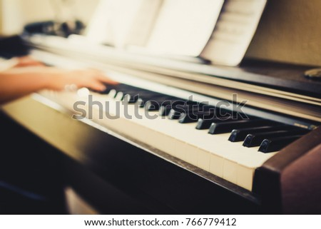 Music background, defocused shot of hands playing piano. Selective focus on piano keys in the foreground.