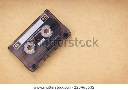 music cassette on retro vintage paper background with copy space - stock photo