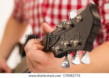 Music, close-up. Musician with a wooden guitar - stock photo