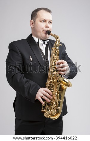 Music Concept and Ideas. Portrait of Caucasian Player in Suit Playing on Saxophone.Vertical Image - stock photo
