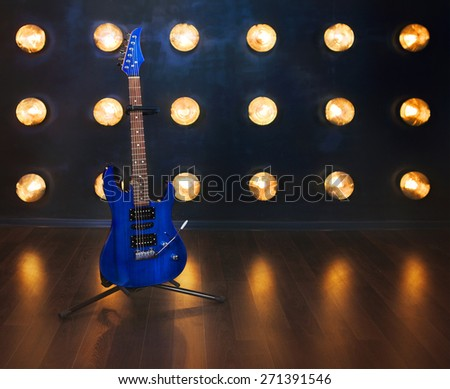 Music concept. Blue electric guitar standing on the wooden floor near the wall under beam of lights - stock photo